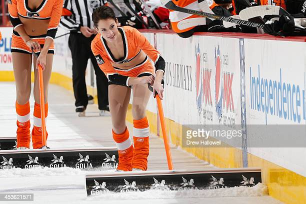 A member of the Philadelphia Flyers ice girls cleans during the game against the Ottawa Senators at the Wells Fargo Center on November 19 2013 in...