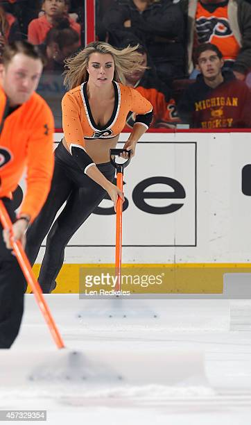 A member of the Philadelphia Flyers ice girls cleans the ice during a timeout against the Montreal Canadiens on October 11 2014 at the Wells Fargo...