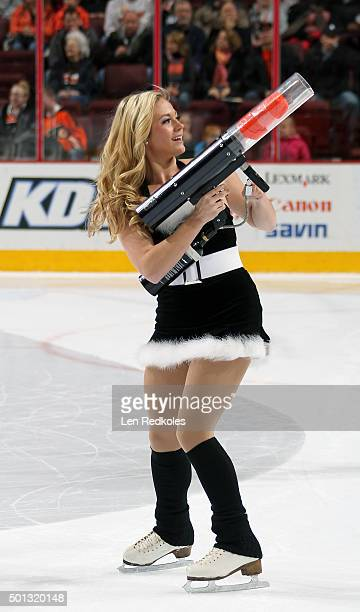 A member of the Philadelphia Flyers ice girls shoots tshirts into the crowd during the first period intermission at a NHL game against the New York...