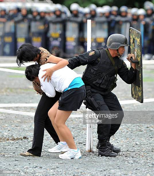 A member of the Philippine elite police covers two colleagues acting as freed hostages during a hostage exercise at a police camp in Manila on...