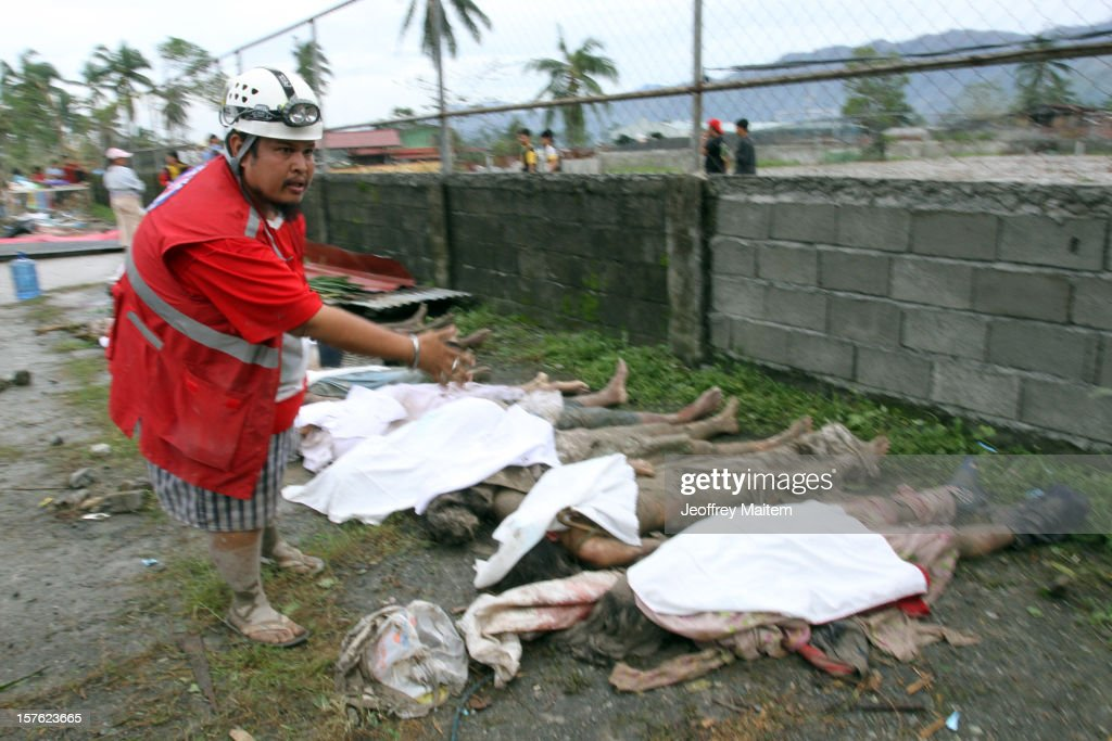 A member of the Philippine Red Cross counts flood victims' bodies at the compound of municipal gymnasium on December 5, 2012 in the southern Philippine township of New Bataan, Compostela province, Philippines. More than 100 people have been killed and scores of others remain missing after Typhoon Bopha, the strongest storm to hit the Philippines this year, pounded the region.