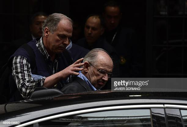 A member of the police assists former IMF head and ex economy minister with Spain's ruling conservative party Rodrigo Rato who has already been...