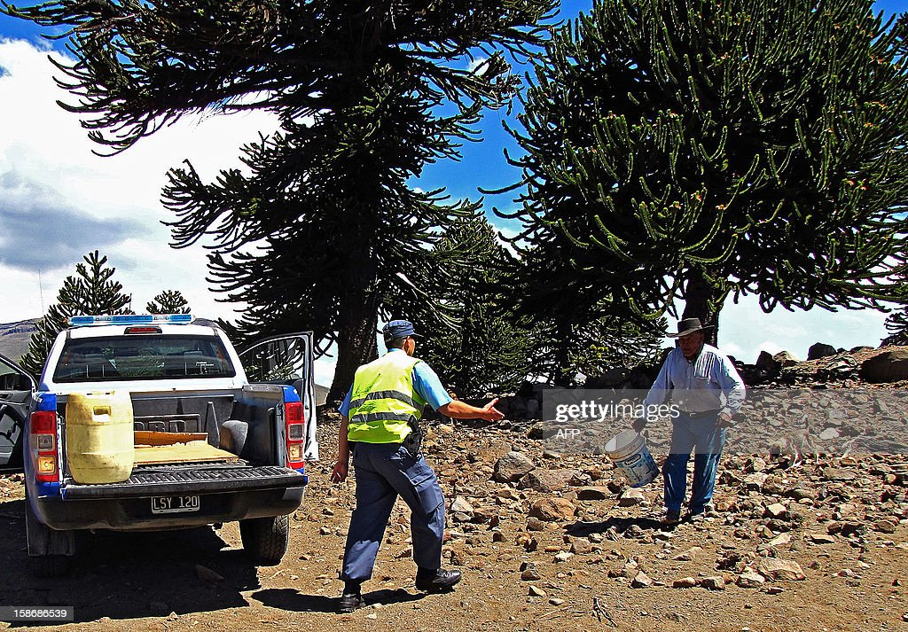 A member of the police (C) delivers water to a local, as the Copahue volcano spews ashes nearby in Caviahue, Neuquen province, Argentina, some 1500 km southwest of Buenos Aires on December 23, 2012. The authorities of Chile and Argentina issued alerts in each country due to the eruption of the Copahue volcano, placed on the border between both countries.