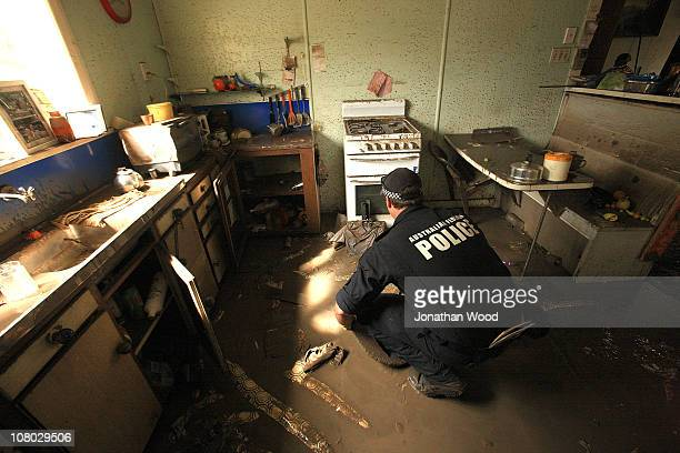 A member of the police force helps clean out a home in the suburb of Fairfield on January 14 2011 in Brisbane Australia Residents returned home to...