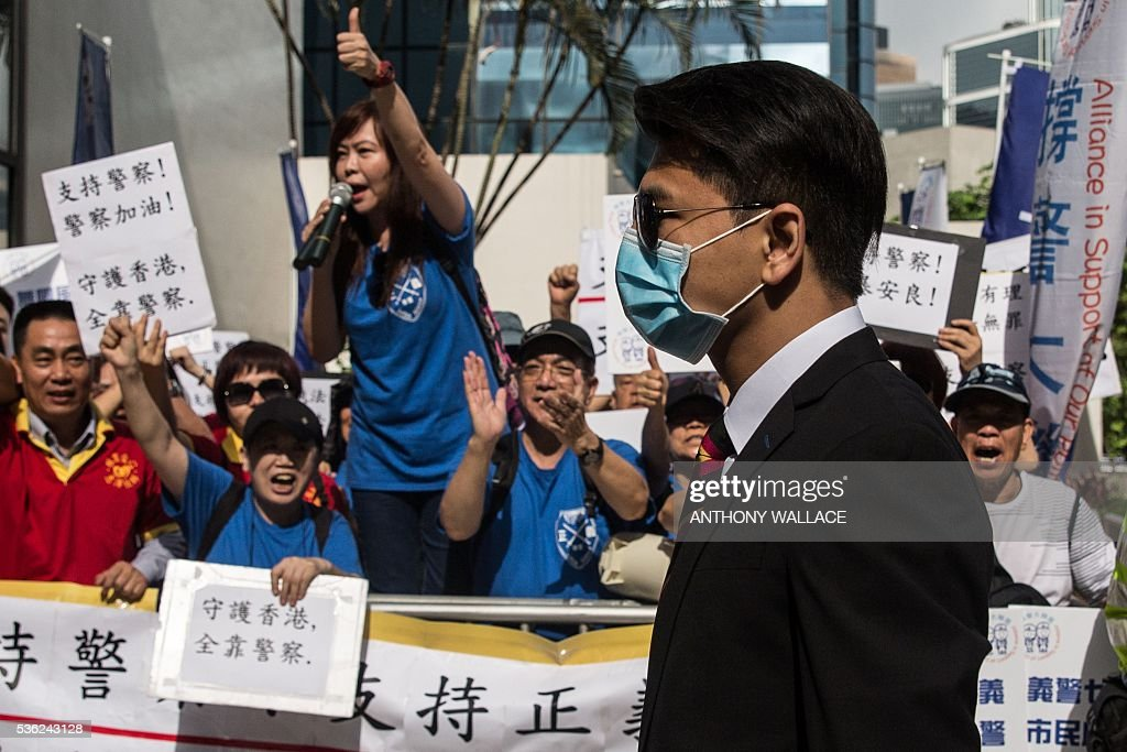 A member of the police (front, wearing mask), who with six colleagues allegedly beat Civic Party activist Ken Tsang (not pictured) during the 2014 pro-democracy protests, walks past pro-police protesters (back) upon his arrival outside the District Court in Hong Kong on June 1, 2016. Seven Hong Kong police officers appeared in court on June 1 over the beating of a pro-democracy protester during mass rallies in 2014, an incident which was captured on film and beamed around the world. / AFP / ANTHONY