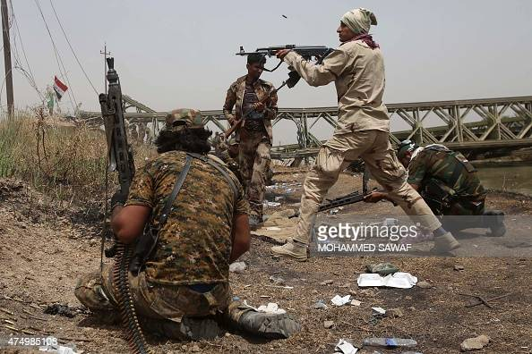 A member of the Popular Mobilisation units opens fire during fightings against Islamic State militants in the area of Sayed Ghareeb near Dujail some...