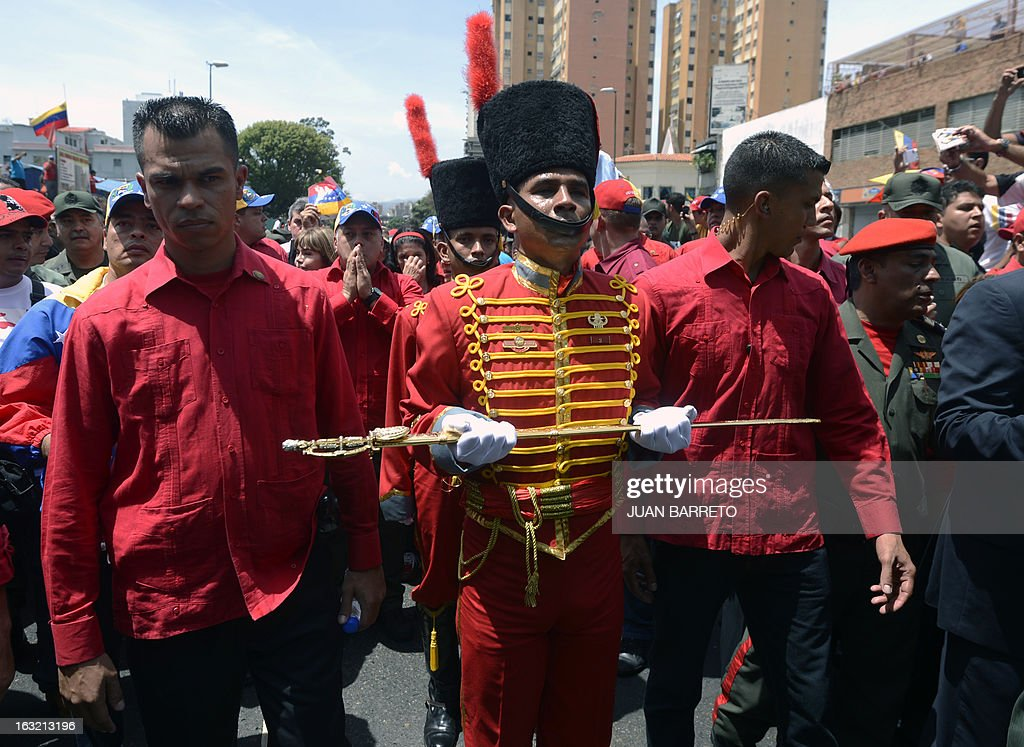 A member of the Presidential Guard of Honor holds a replica of Simon Bolivar's sword while accompanying the hearse carrying the coffin of Venezuelan President Hugo Chavez on its way to the Military Academy, on March 6, 2013, in Caracas. Venezuela was plunged into uncertainty Wednesday after the death on the eve of President Hugo Chavez, who dominated the oil-rich country for 14 years and came to embody a resurgent Latin American left. AFP PHOTO/Juan BARRETO