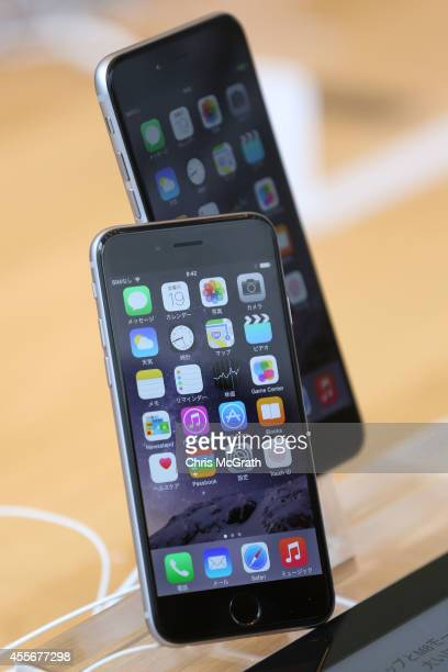 A member of the press compares the new iPhone models at the launch of the new Apple iPhone 6 and iPhone 6 plus at the Apple Omotesando store on...