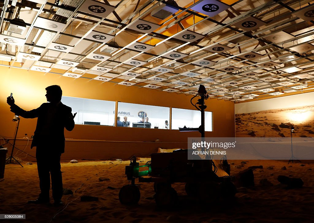 A member of the press speaks into his phone by a prototype Mars rover in a simulated Mars environment at the Airbus Defence and Space company in Stevenage on April 29, 2016. British astronaut Major Tim Peake will remotely navigate the rover through the Martian landscape from the International Space Station, part of a project to learn how astronauts can control remote systems. / AFP / ADRIAN