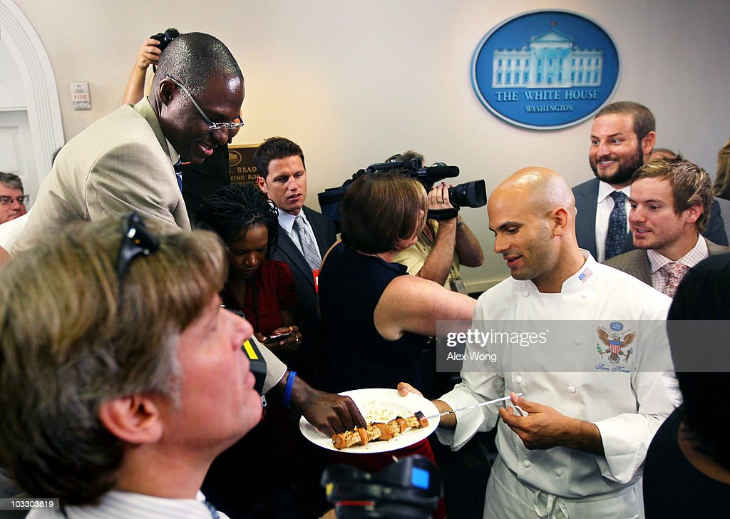 A member of the press takes a piece of seafood sample from White House chef Sam Kass (R) as members of the New Orleans Saints invite the media to taste seafood samples from Gulf of Mexico at the White House briefing room following a reception for the 2010 National Football League Super Bowl champions August 9, 2010 in Washington, DC. The Saints, lead by head coach Sean Payton, finished the 2009-2010 season with a winning record of 13-3 and defeated the Indianapolis Colts to take the championship.