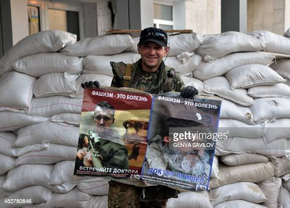A member of the proUkraine Donbass Battalion holds propaganda posters depicting Igor Girkin Defence minister of the selfcalled People's Republic of...