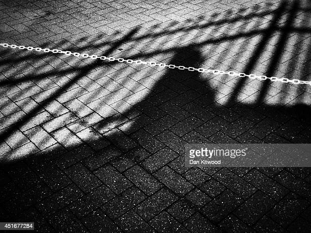 A member of the public casts a shadow as he walks the queue during the Wimbledon Championships at the 'All England Lawn Tennis and Croquet Club' on...