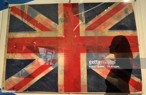 A member of the public casts a shadow on a Union flag recovered from Ground Zero amongst the wreckage of the 9/11 attack on New York's World Trade...