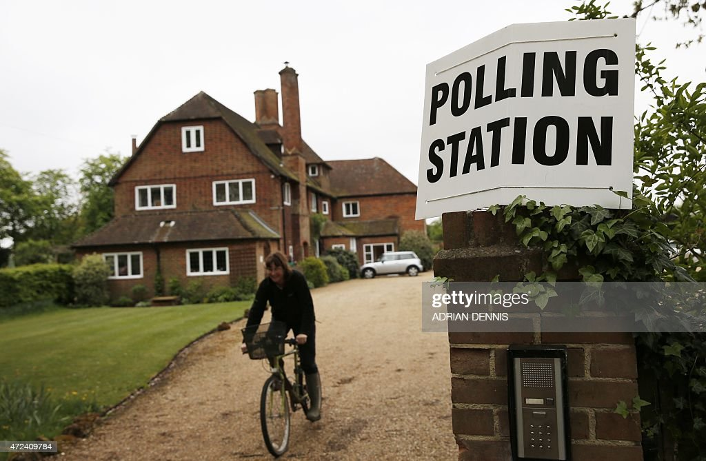 A member of the public cycles away after casting her vote at a polling station in a residential house in Bramshill in southern England, on May 7, 2015, as Britain holds a general election. Polls opened today in Britain's closest general election for decades with voters set to decide between the Conservatives of Prime Minister David Cameron, Ed Miliband's Labour and a host of smaller parties.