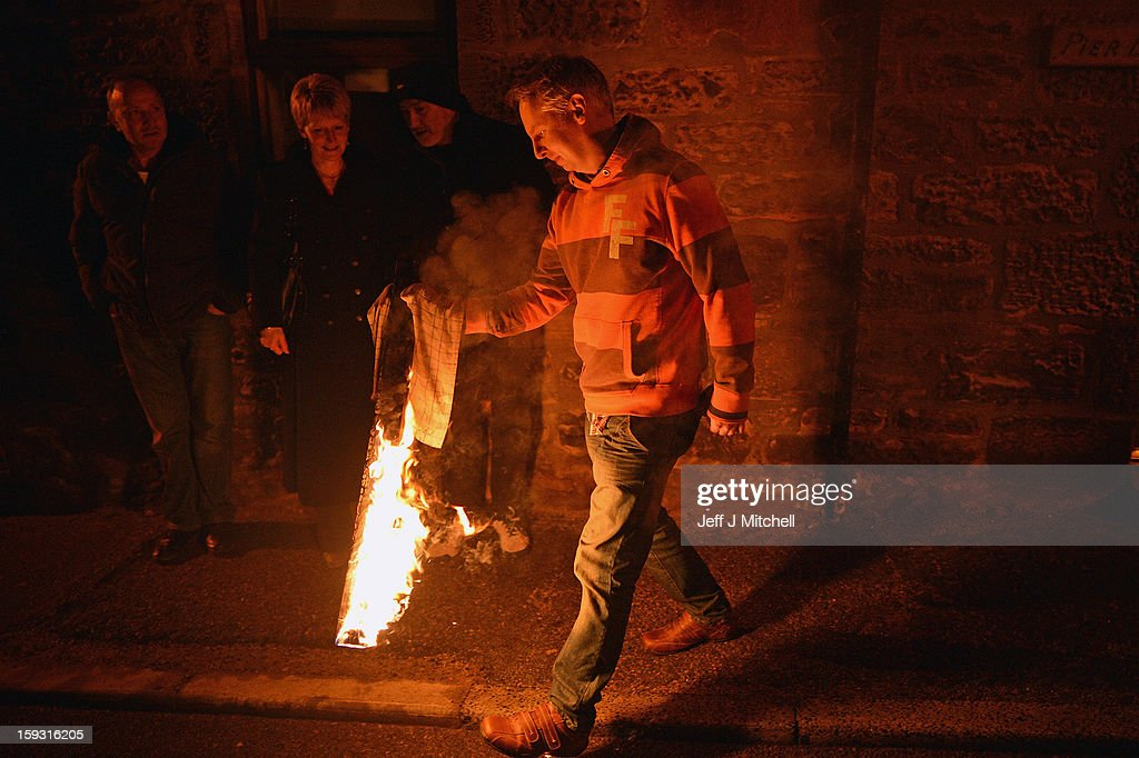 A member of the public holds a piece of the Clavie after being given it by the Clavie Crew on January 11, 013 in Burghead, Scotland. The burning of the Clavie takes place on January 11 each year as local people welcome in the New Year with a fire ceremony, which has ancient roots believed to bring good luck for the coming year.
