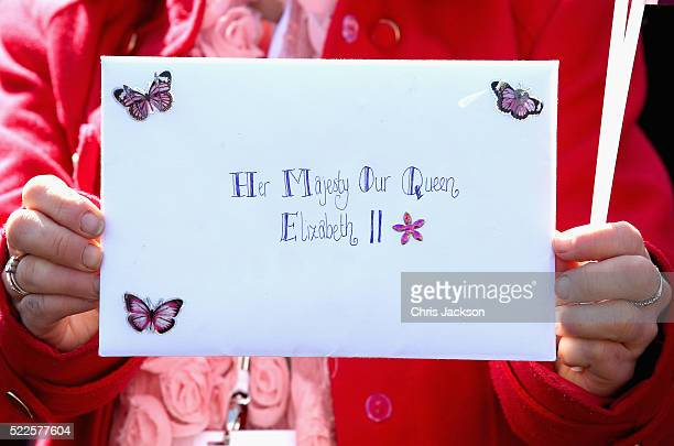 A member of the public holds up a card for Queen Elizabeth II as she visits the Queen Elizabeth II delivery office in Windsor with Prince Philip Duke...