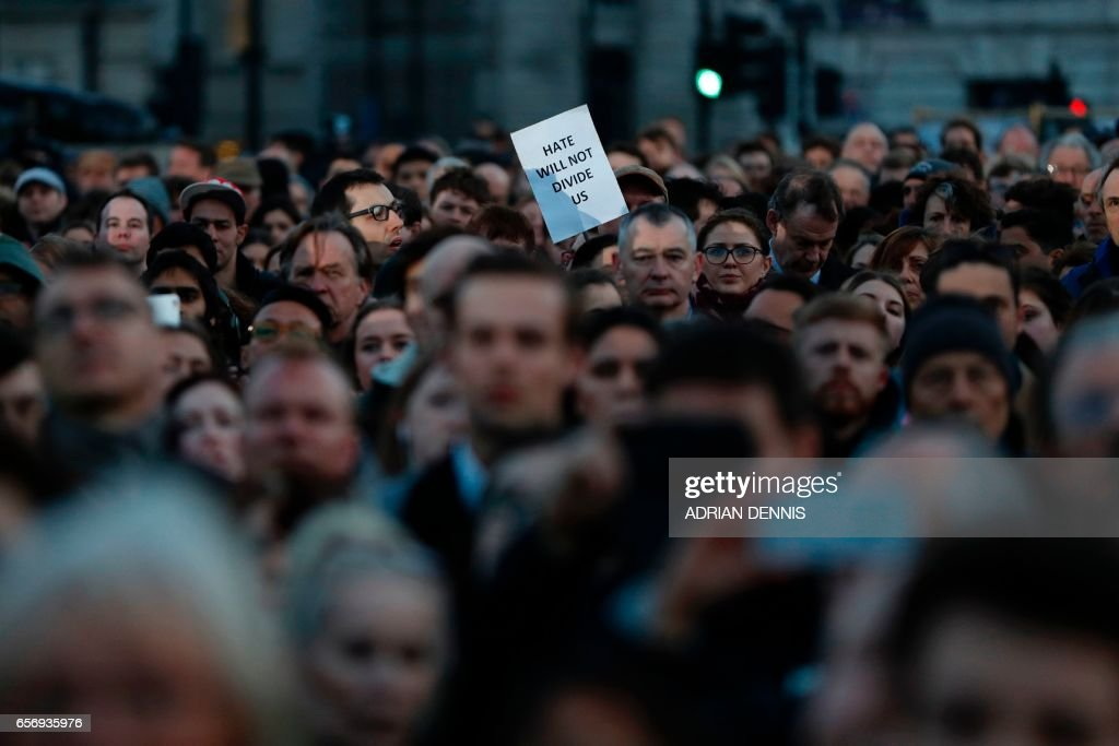 TOPSHOT - A member of the public holds up a sign reading 'hate will not divide us' during a vigil in Trafalgar Square in central London on March 23, 2017 in solidarity with the victims of the March 22 terror attack at the British parliament and on Westminster Bridge. Britain's parliament reopened on Thursday with a minute's silence in a gesture of defiance a day after an attacker sowed terror in the heart of Westminster, killing three people before being shot dead. Sombre-looking lawmakers in a packed House of Commons chamber bowed their heads and police officers also marked the silence standing outside the headquarters of London's Metropolitan Police nearby. PHOTO / Adrian DENNIS