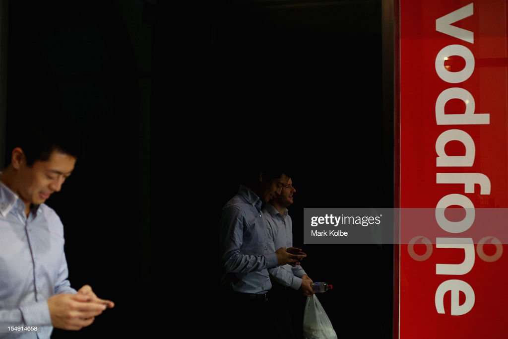 A member of the public is seen using a mobile phone as he walks past a city Vodafone store on October 29 2012 in Sydney Australia Vodafone Australia...