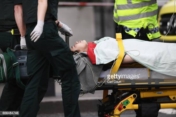 A member of the public is taken away for treatment by emergency services near Westminster Bridge and the Houses of Parliament on March 22 2017 in...
