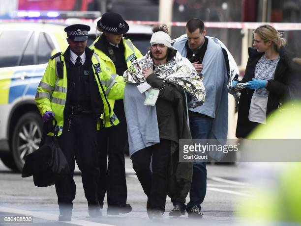 A member of the public is treated by emergency services near Westminster Bridge and the Houses of Parliament on March 22 2017 in London England A...