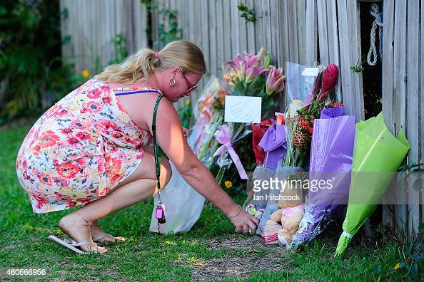 A member of the public lays a a bunch of flowers across the road from the scene of a multiple stabbing in the suburb of Manoora on December 19 2014...