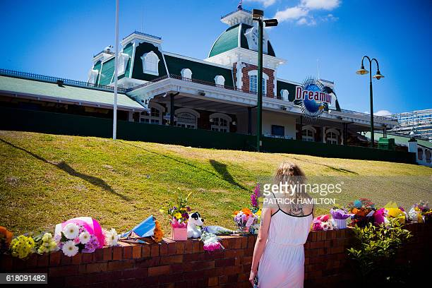 A member of the public lays flowers at a makeshift floral tribute a day after four people were killed when a raft flipped at the Dreamworld theme...