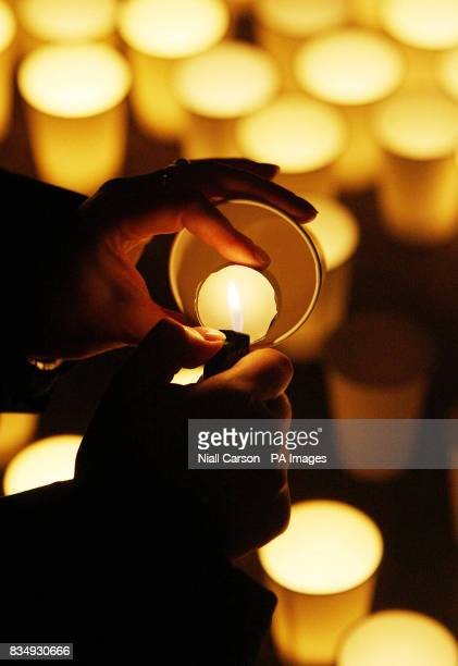 A member of the public lights a candle during a candlelit vigil outside Leinster House in Dublin tonight as part of the campaign to reverse cuts to...