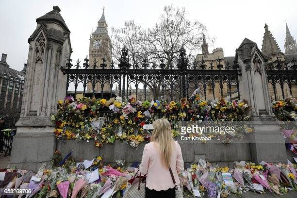 A member of the public looks at the flowers which have been left outside the Houses of Parliament in memory of those who died in last weeks...