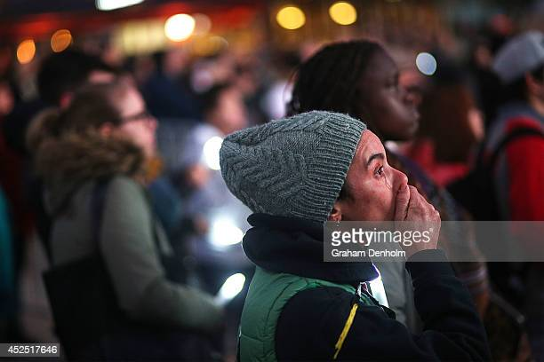 A member of the public mourns the victims of HIV/AIDS and the victims of flight MH17 during a candlelight vigil at Federation Square on July 22 2014...