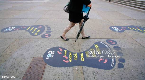 A member of the public passes the giant footprints that mark the Government's Act on CO2 campaign in Trafalgar Square London