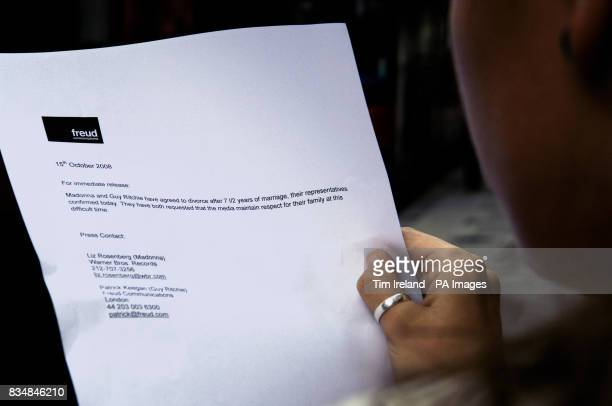 A member of the public reads a copy of the press release confirming the divorce of Madonna and Guy Ritchie