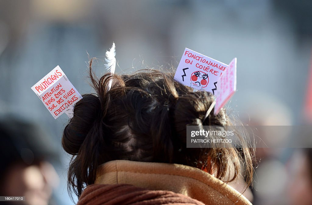 A member of the public sector (education, health and finance) wears signs in her hair reading 'Politicians be aware you are on ejectable seats' 'public service employees angry' as she takes part on January 31, 2013 in a national day of protest in Strasbourg, eastern France, against the French government's social policy. For the first time since French President Francois Hollande's election, three labour unions (CGT, FSU, Solidaires) called on 5.2 million civil servants to stop working to show to the government their unhappiness, particularly in terms of purchasing power. AFP PHOTO / PATRICK HERTZOG