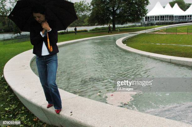 A member of the public shelters on the The Princess Diana Memorial Fountain after it flooded the day after it was officially opened by the Queen...