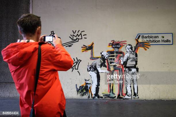 A member of the public takes a photograph of a new work by street artist Banksy on a wall by the Barbican Centre on September 18 2017 in London...