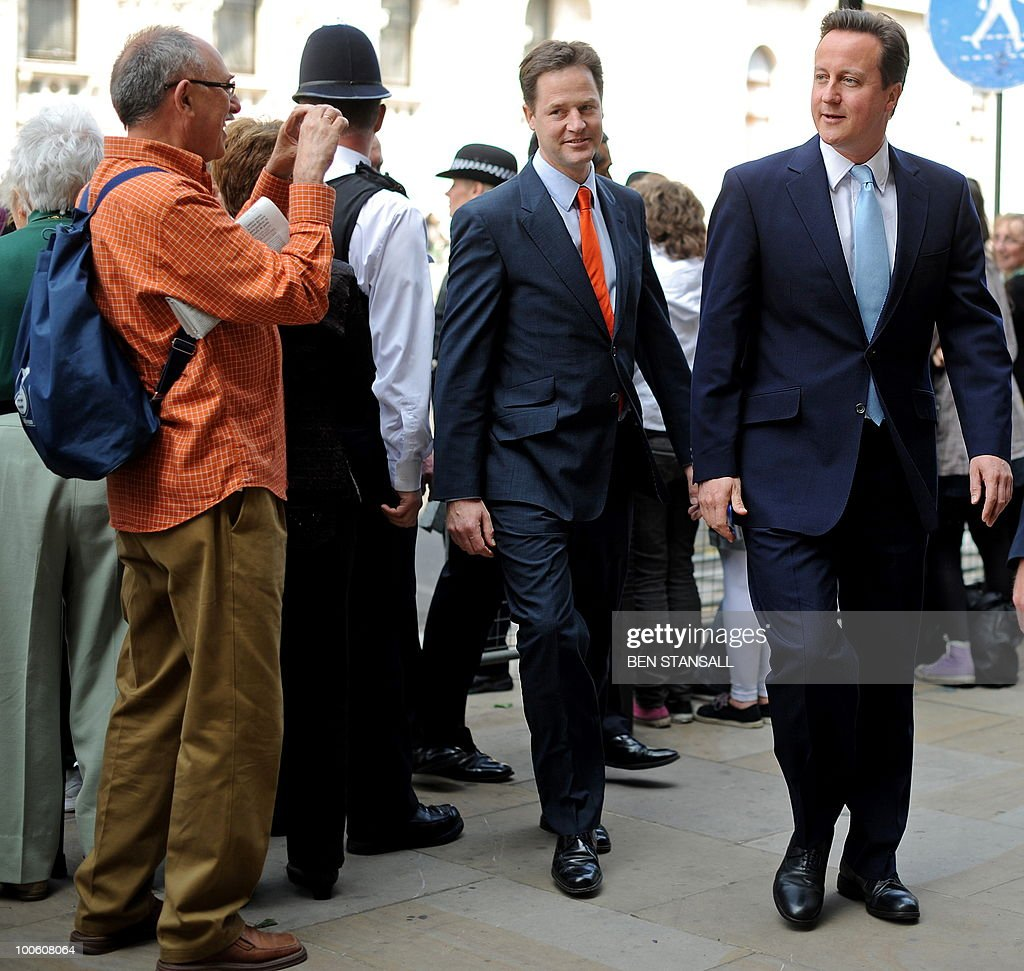 S BYLINE A member of the public (L) takes a photograph of Britain's Conservative Prime Minister, David Cameron (R), and Liberal Democrat Deputy Prime Minister, Nick Clegg (2nd L), as they walk to the Houses of Parliament to attend the State Opening of Parliament, in central London on May 25, 2010. Britain's Queen Elizabeth II set out the new coalition government's legislative programme on Tuesday in a ceremony of pomp and history following the closest general election for decades. AFP PHOTO/Ben Stansall