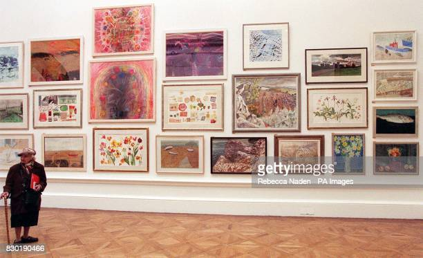 A member of the public views the exhibited paintings at a preview of the Summer Exhibition being held at The Royal Academy of Art London from early...