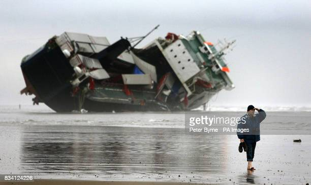 A member of the public walks on the beach past the Irish ferry 'Riverdance' that run aground in Blackpool last week