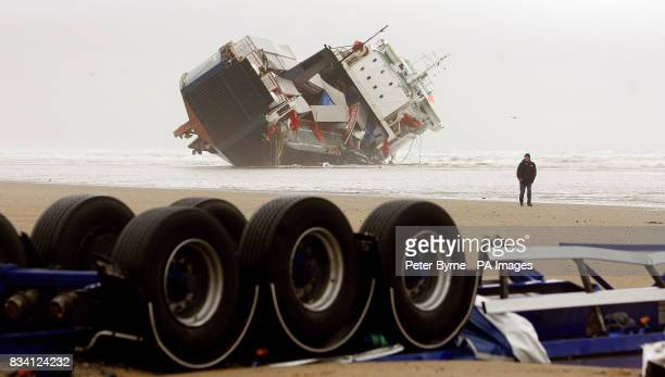 A member of the public walks on the beach past the Irish ferry 'Riverdance' that run aground in Blackpool last week The wheels of a container lorry...