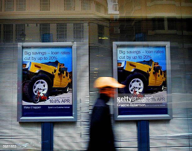 A member of the public walks past posters advertising mortgages and loans at low intrest rates October 30 2003 London Britons piled on debt at a...
