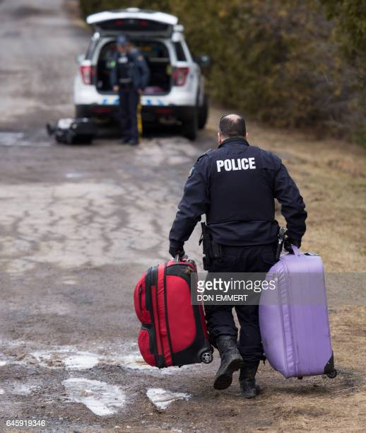 A member of the RCMP carries luggage belonging to a couple who claimed to be from Turkey after they crossed the US/Canada border and were arrested...