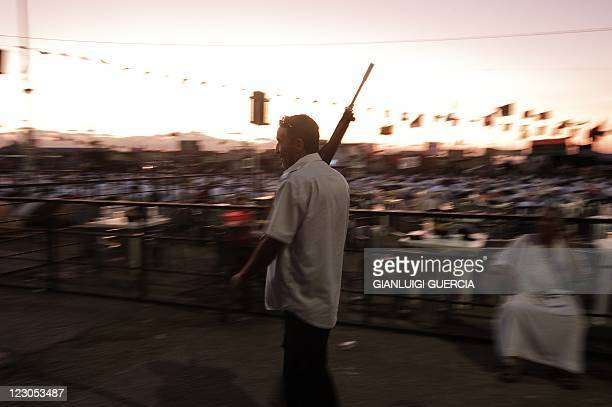 A member of the rebel's security forces patrols on the streets as hundreds attend the evening prayer before breaking fast at Freedom square in the...