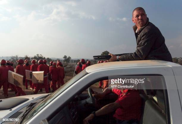 A member of the 'Red Ant Security Relocation and Eviction Services' rides atop a pickup truck on July 4 with his shotgun as other members of the Red...