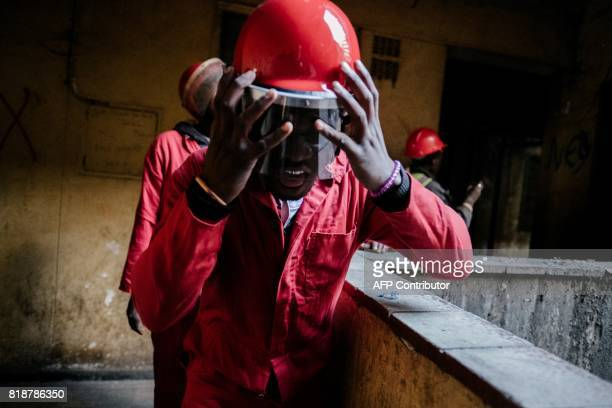 A member of the Red Ants a municipal team tasked with evictions adjusts his helmet during an eviction inside the Fattis Mansion in downtown...