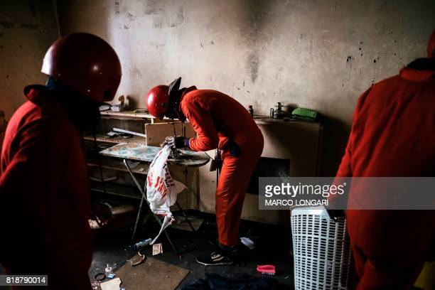 A member of the 'Red Ants' a municipal team tasked with evictions looks at jewellery left behind by residents during an eviction inside the Fattis...