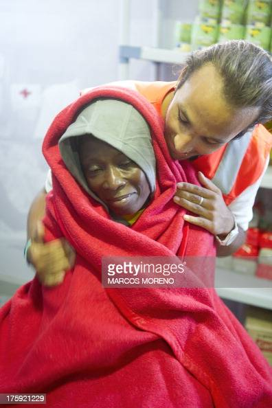 A member of the Red Cross tends to a wouldbe immigrant wrapped in a blanket at the Red Cross premises at Tarifa's harbour on August 10 after 86...