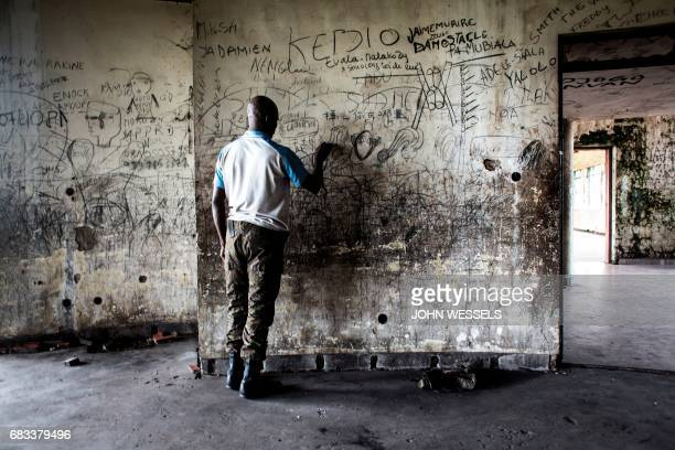 A member of the Republican Guard is seen scribbling on the wall inside the derelict palace of the former president of the Democratic Republic of the...