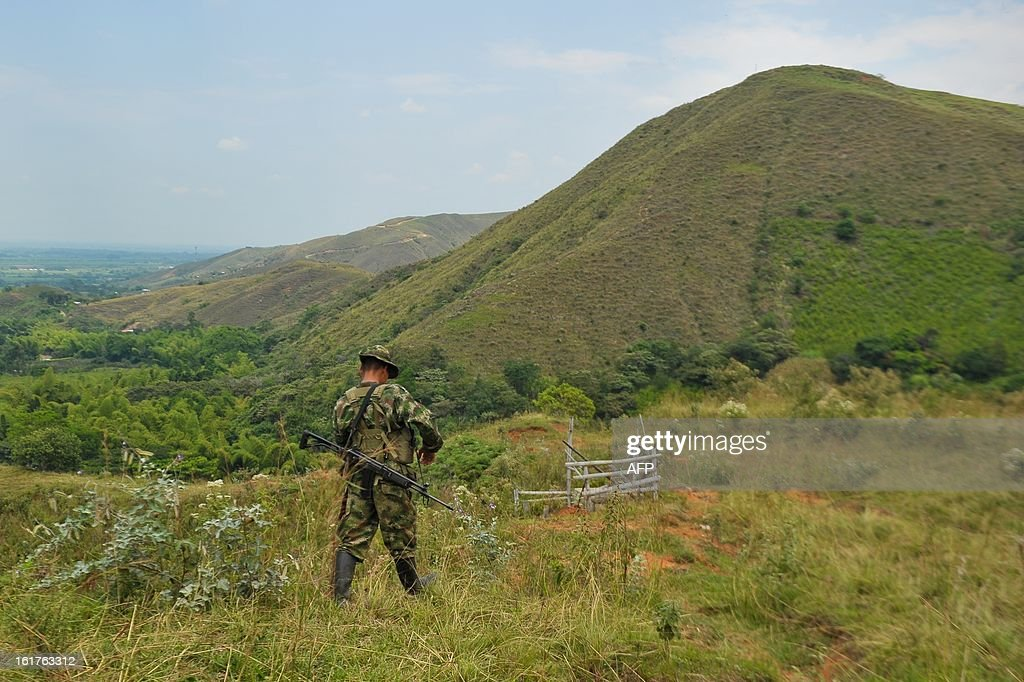 A member of the Revolutionary Armed Forces of Colombia (FARC) guerrillas, guards the mountainous region of the department of Cauca, around Montealagre, Colombia, on February 15, 2013 after they released Colombian police officers Victor Alfonso Gonzalez and Cristian Camilo Yate. Leftist Colombian guerrillas on Friday released two police officers they had held for three weeks, the International Committee of the Red Cross said. The men were released in a rural area in Cauca department in southwestern Colombia and were in good health, the ICRC said in a statement. AFP PHOTO / LUIS ROBAYO