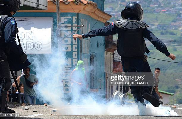 A member of the riot police kicks a tear gas bomb during a protest by students opponent to Nicolas Maduro's government in San Cristobal state of...