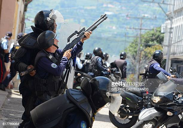 A member of the riot police shoots into the air during a protest by students opponent to Nicolas Maduro's government in San Cristobal state of...