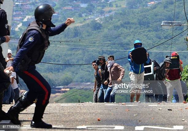 A member of the riot police throws a tear gas bomb during a protest by students opponent to Nicolas Maduro's government in San Cristobal state of...